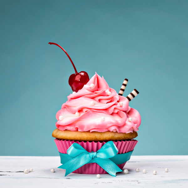 pink frosted swirl cupcake with cherry and ribbon
